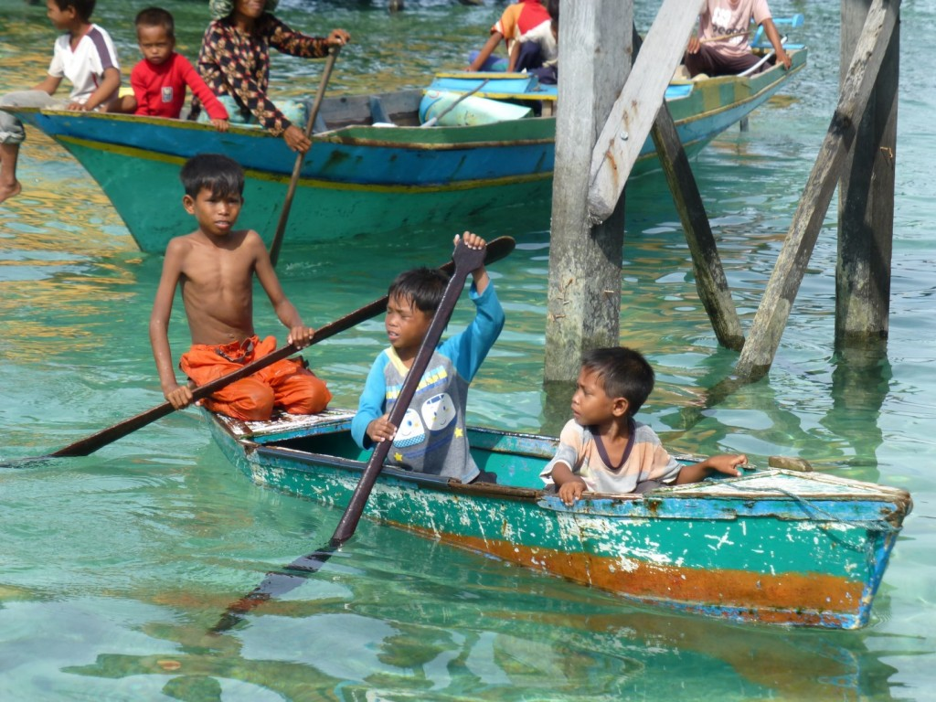 local kids from Mabul paddle over to the huts to beg for money