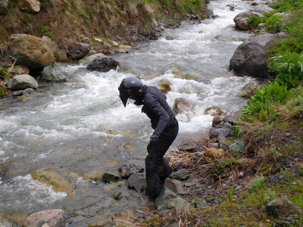 Me washing all the mud off my boots in a stream